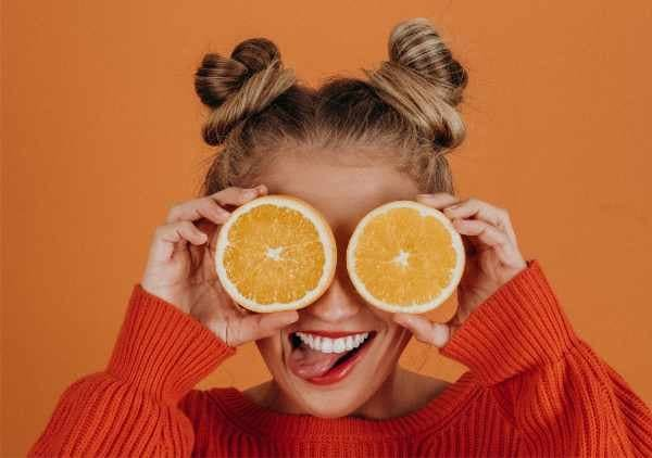 Girl being silly with an orange